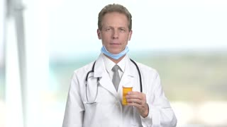 Handsome mature doctor with medicine. Smiling male doctor with bottle of medicine. Mature male doctor showing thumb up. Medical products advertisement.