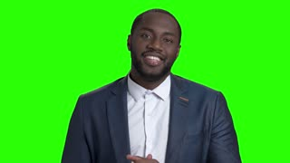 Handsome smiling macho-man on green screen. Sexy african american businessman seductively looking at camera on Alpha Channel background. Temptation and masculinity concept.