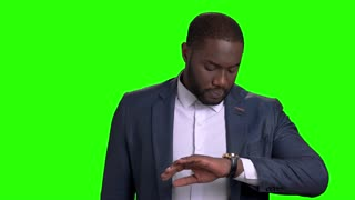 Handsome well dressed businessman checking time on watch. Confident afro-american entrepreneur looking at his wrist watch on chroma key background. Time is money concept.