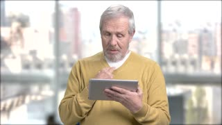 Happy aged man using pc tablet. Cheerful elderly man talking via internet using digital tablet, blurred background.