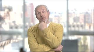 Happy bearded man on blurred background. Male senior got an idea on window city background. Positive older man.