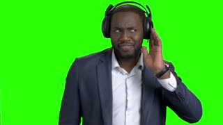 Happy businessman in headphones listening to music. Cheerful afro american guy in business suit is dancing on chroma key background. Relax at work.