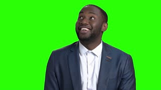 Happy businessman is looking around on green screen. Happy confused afro-american man in business suit on Alpha Channel background.