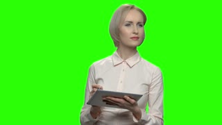 Happy businesswoman working with a pen on a tablet. Look forward and rewriting. Green screen hromakey background for keying.