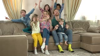 Happy caucasian family watching tv. People smiling and celebrating.
