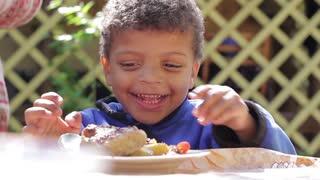 Happy child eats meat. Kid eating chicken. Black boy is appetizing eats. Funny boy.