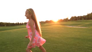 Happy child running over green meadow. Slow motion joyful little girl in cute dress having fun on beautiful nature background, sunset sky. Childhood and weekend in countryside.