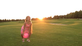 Happy child throwing ball on green lawn. Slow motion joyful girl in beautiful dress playing ball outdoors at sunset. Kids energy and emotions.