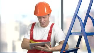 Happy construction worker with pc tablet. Smiling builder in uniform using digital tablet and looking at camera. People, repair and construction concept.