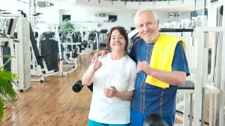 Happy couple of seniors gesturing thumb up. Smiling elderly people showing thumb up at gym. Sport and seniors.