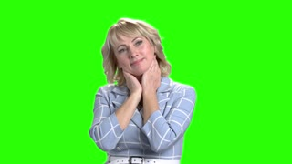 Happy dreaming woman on green screen. Thinking business lady is smiling on chroma key background. Pretty woman is meditating.