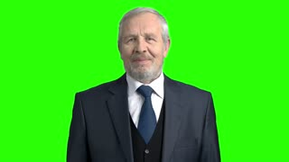 Happy elderly businessman on green background. Senior man in grey suit and tie smiling on chroma key background, slow motion. Old cheerful businessman.