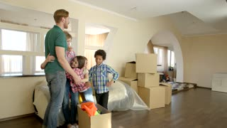 Happy family hugging indoors. People and cardboard boxes, room. Stress free moving.