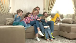 Happy family on the sofa. Smiling adults and children indoors.
