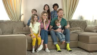 Happy family watching tv. Joyful people sitting on sofa. Most popular television channels.
