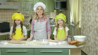 Happy female chef and kids. Smiling people in the kitchen. Food and cooking shows.