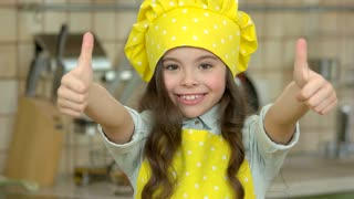 Happy girl in chef uniform. Smiling child showing thumb up. What makes a great cook.