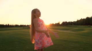Happy girl on green meadow. Slow motion cheerful kid outdoors having fun, sunset sky. Childhood and carefree.