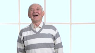 Happy laughing senior, blurred background. Beautiful old man laugh on window background. Wonderful mood and emotions.