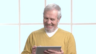 Happy male senior with pc tablet. Smiling mature man working on pc tablet indoors.