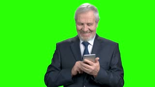 Happy manager typing a message on smartphone. Smiling senior businessman with modern cell phone on green screen.