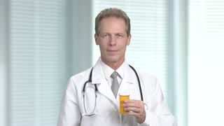 Happy mature doctor, blurred background. Male doctor in white coat holding container with pills at hospital. Middle aged doctor showing thumb up gesture.