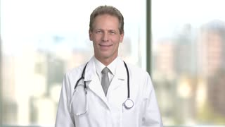 Happy mature doctor portrait. Glad physician adult man in medical coat and stethoscope. Bright abstract blurred windows background with view on city.