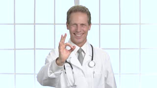 Happy medical specialist gesturing ok. Professional male doctor showing ok sign with fingers. Handsome male doctor.