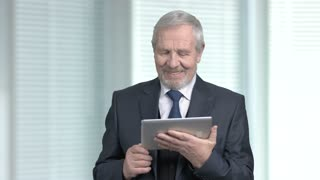 Happy older businessman using pc tablet. Cheerful senior man in formal wear having conversation via internet. Hello there concept.