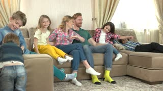 Happy parents and children, slow-mo. Smiling people on the couch.