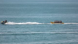 Happy people having fun on banana boat. Cool summer holiday. Entertainment for tourists