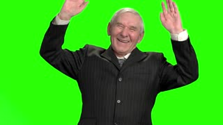 Happy politician puts hands up, slow-motion. Old businessman laughuing hard against green hromakey background.