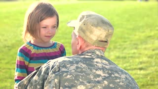 Happy reunion of EU soldier with family outdoors. EU military man hugs daughter.
