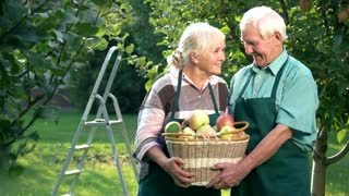 Happy senior couple holding basket. People in aprons smiling. We are home.