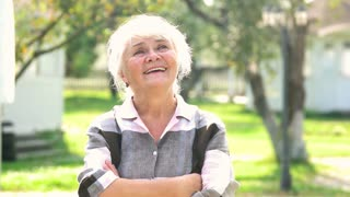 Happy senior woman outdoor. Lady with crossed arms smiling. Positive life tips.