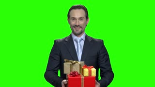 Happy smiling businessman with gifts. Green hromakey background for keying.