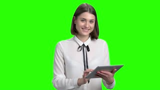 Happy smiling young girl use tablet. Green screen hromakey background for keying.