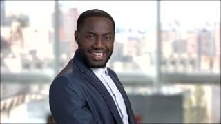 Happy surprised businessman on blurred background. Portrait of smiling dark-skinned man in formal wear.