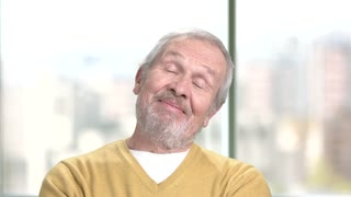 Happy thinking aged man close up. Senior smiling man is dreaming on blurred background. Human facial expressions.