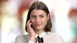 Happy young woman is talking on phone. Smiling girl in a happy conversation, blurred background. Pretty woman flirting via phone.