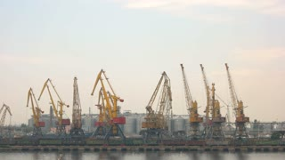 Harbor cranes on sky background. Storage tanks and buildings. Port handling equipment.