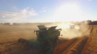 Harvester combines, field and dust. Key to country economy development.