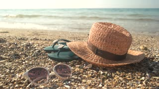 Hat with sunglasses on shore. Flip flops near the sea. It's time to relax.