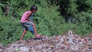 Homeless child wanders through the dump. Beggar boy. Hungry child is look for food in the garbage.