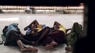 Homeless people sleep on the platform of the train station.
