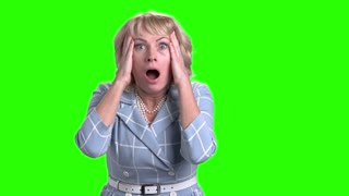 Horrified mature woman on green screen. Caucasian middle-aged woman looking frightened and shocked on chroma key background. Human negative expressions.