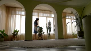 Housemaid at work. Woman water spraying plants.