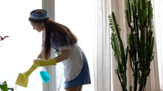 Housemaid is cleaning window. Tired woman wiping forehead. Fatigue symptoms at work.