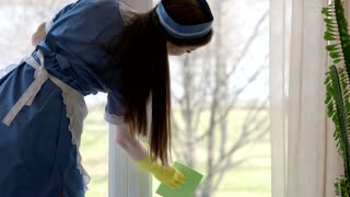 Housemaid wiping a window. Young female at work. Average housekeeping salaries.