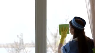 Housemaid wiping window. Young female working.